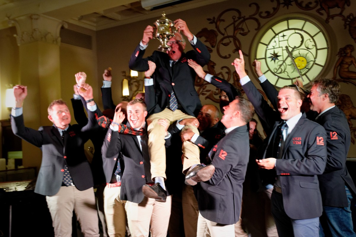 The jubilant VIM (US-15) crew hoists skipper Patrick Howaldt and the newly dedicated Vintage 12mR World Championship | Sailpix.FI